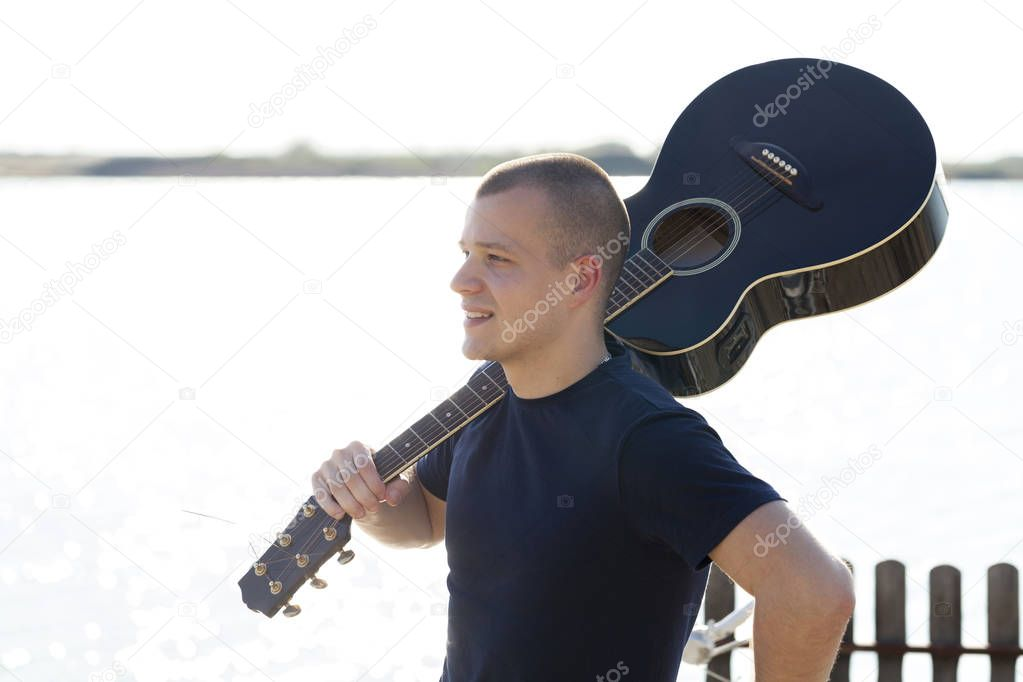 Handsome young man enjoying by the river with a guitar.Selective focus and small depth of field.