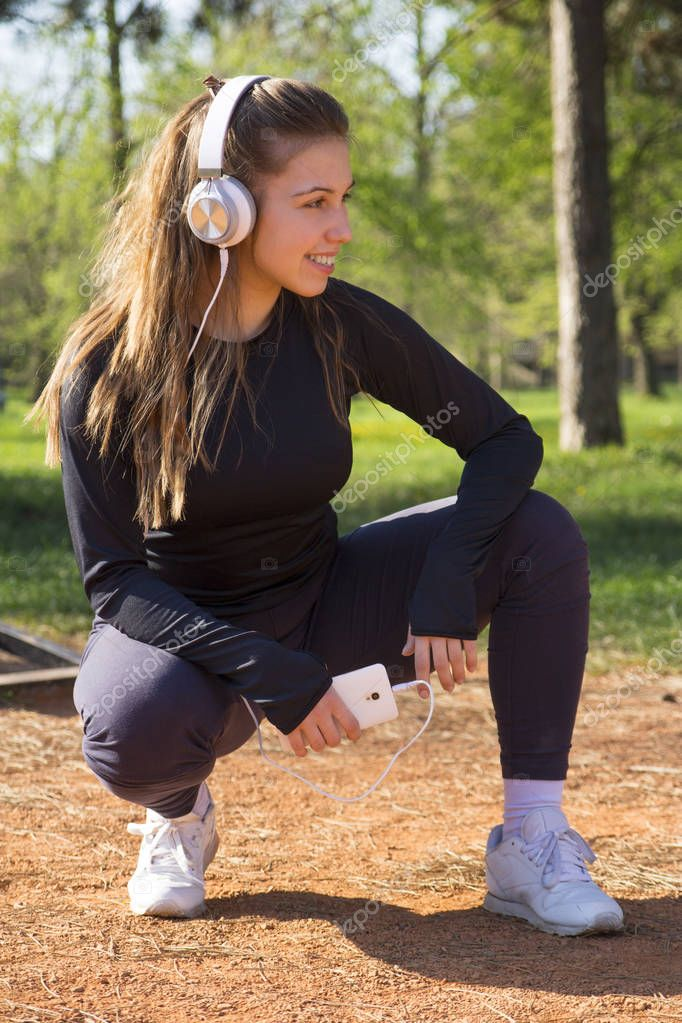Beautiful young woman doing exercises and enjoys listening to music in the park. Selective focus and small depth of field.