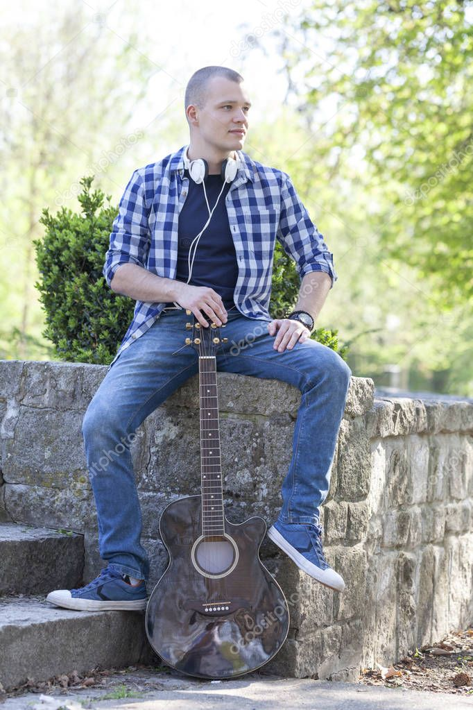 Handsome young man enjoying the park with a guitar.Selective focus and small depth of field.