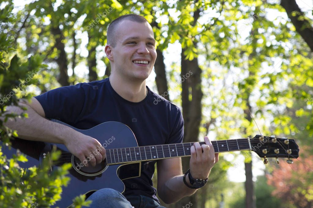 Smiling handsome young man enjoys playing the guitar in the park. Selective focus and small depth of field.