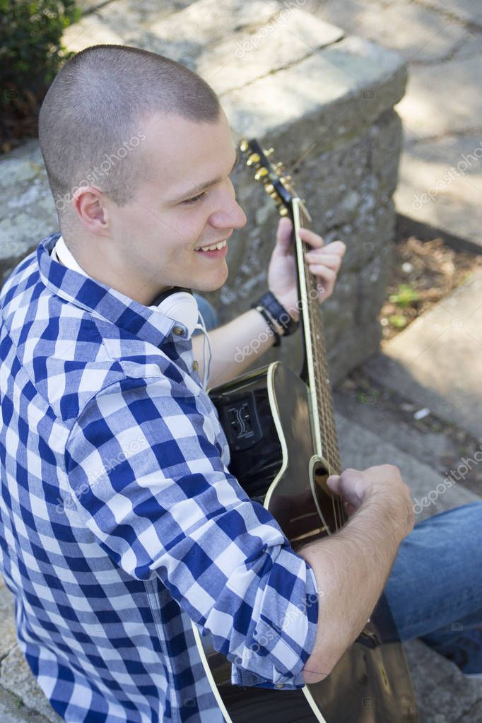 Handsome young man enjoying the park, sitting and playing guitar. Selective focus and small depth of field.