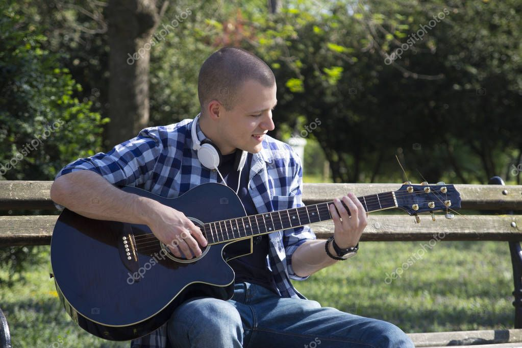 Young man sits on a park bench and playing guitar.Selective focus and small depth of field.