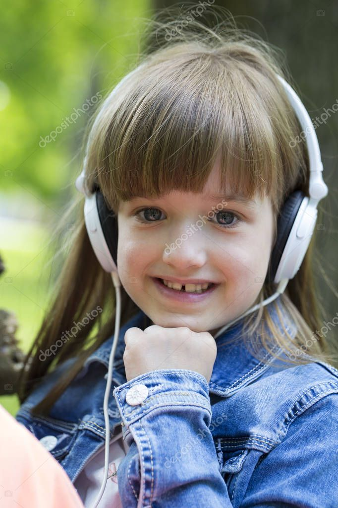 Beautiful little girl listens to music and enjoying the park.
