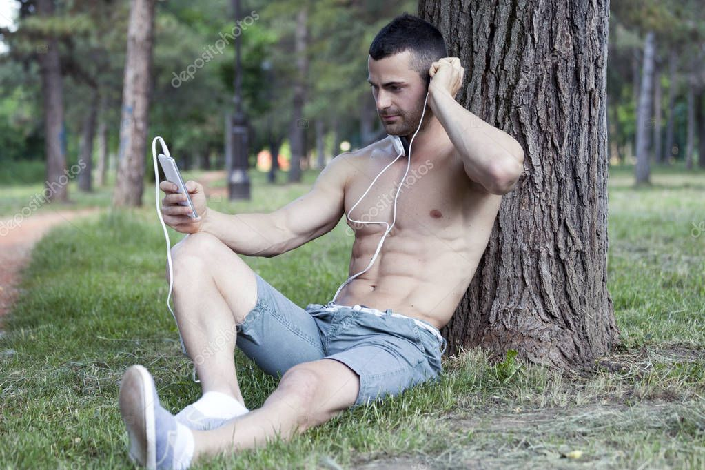 Handsome  and attractive young man sitting in a park, resting after training. Listening to music and looking at mobile phone