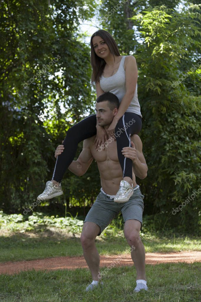 Young loving couple, men and women enjoy together while exercising in a park. She sits on his shoulders, but he does squats. He is very strong