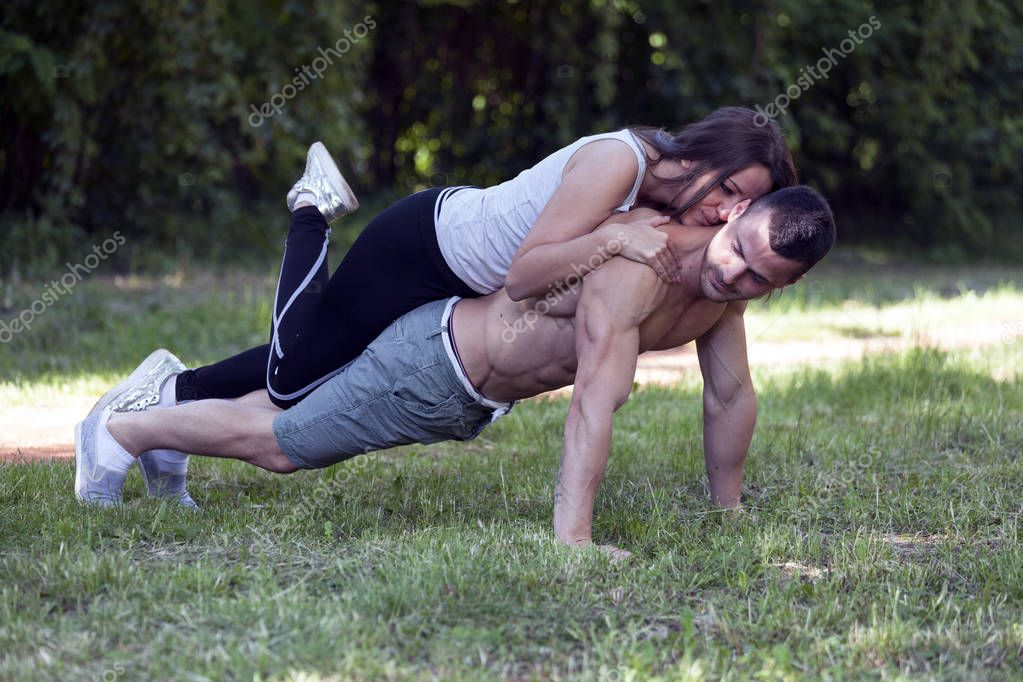 Young loving couple, man and woman enjoy while exercising together in the park. They perform acrobatics