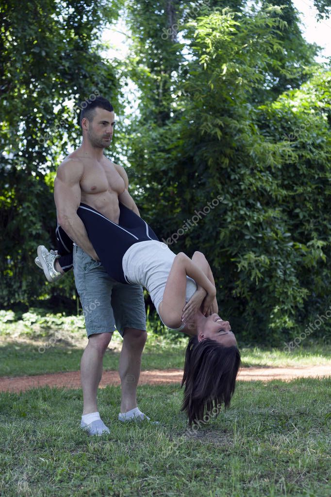 Young loving couple, man and woman, exercising together. She does sit-ups while he holds