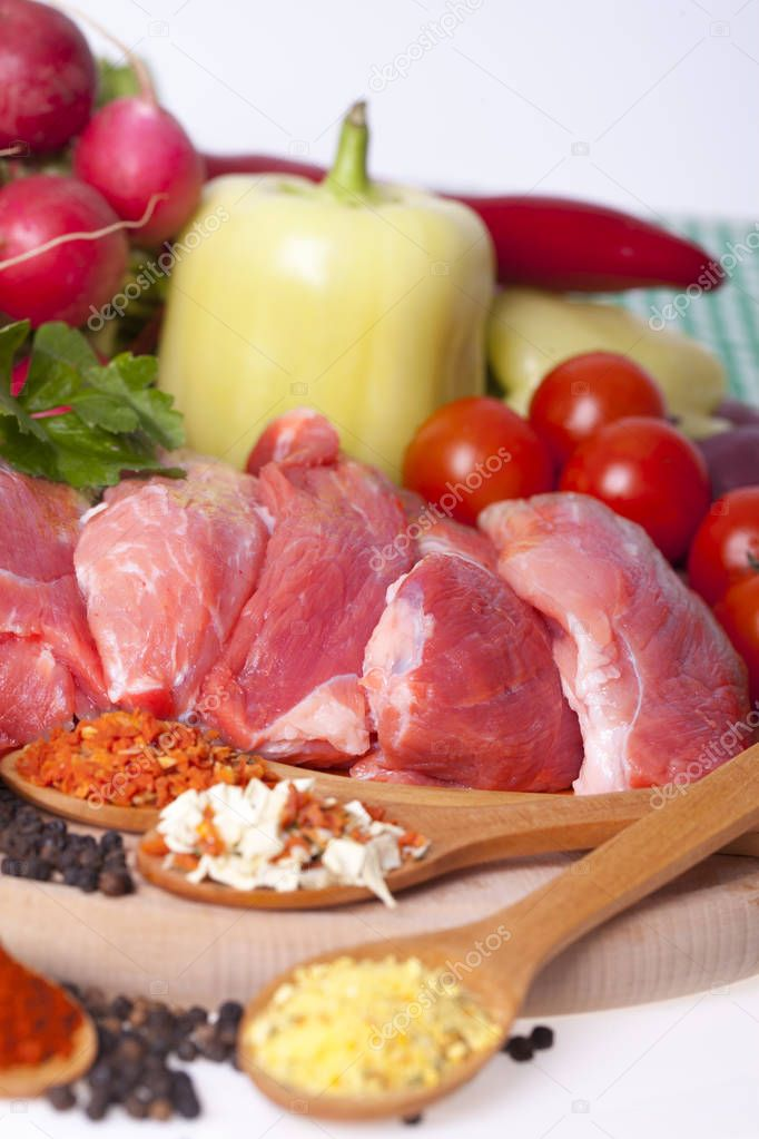 Fresh pork with vegetables and spices on a wooden board. Raw meat, cut into pieces with pepper, cherry, radish, pepper and various spices in wooden spoons