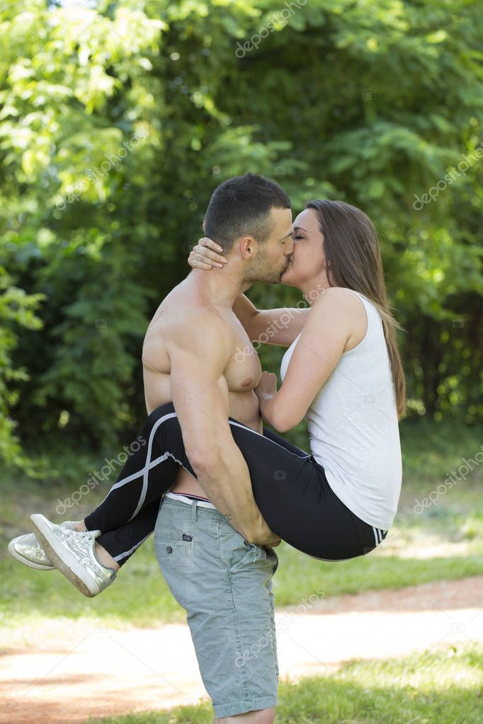 Young happy couple, man and woman exercising in the park. They are  kissing in the park.Lovely, Emotional And Romantic Moments