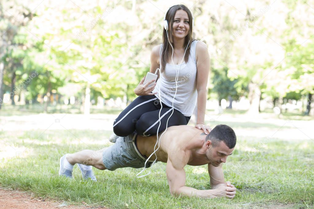 Young happy couple, man and woman, exercise work together and prepare for the competition. They perform acrobatics.She sits on his back while he was doing push-ups