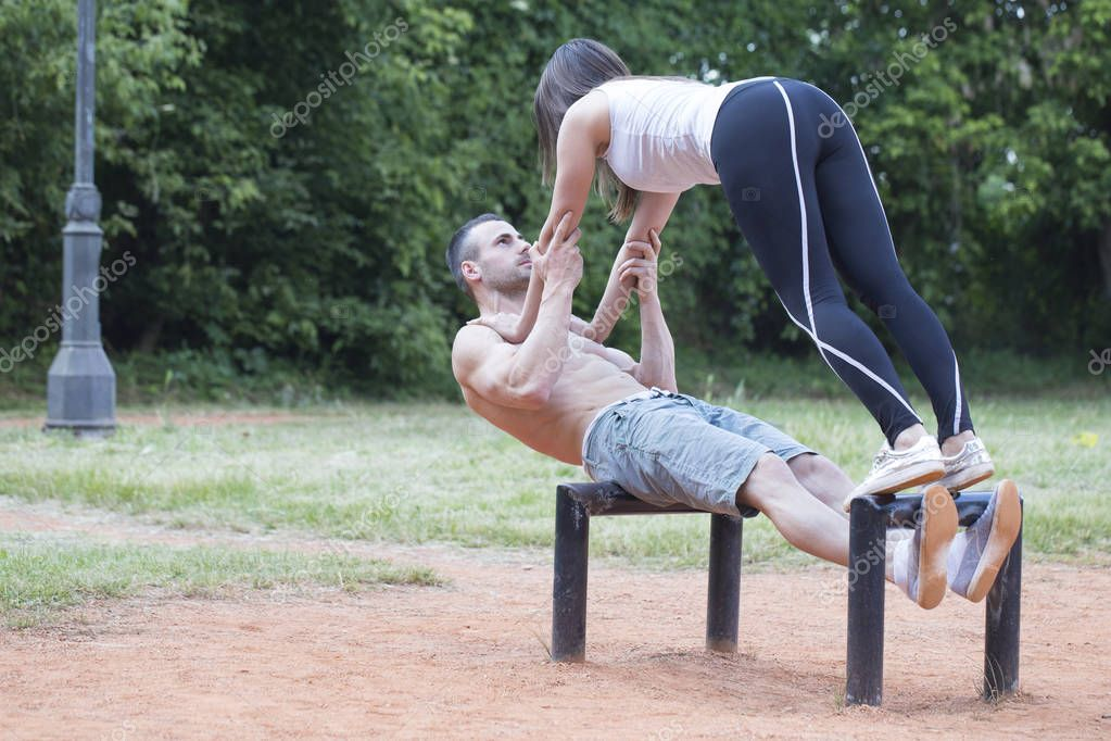 Young happy couple, man and woman exercising in the park. They very much like to train together and perform acrobatics.