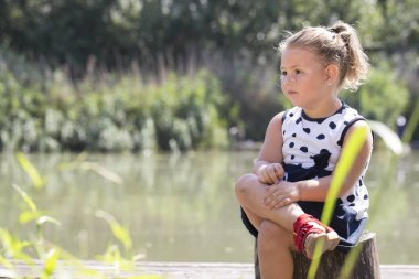 Portrait of a cute little girl in a dress while sitting next to the river. She plays on a beautiful sunny summer day. Child happiness, joy, growing up. Copy space