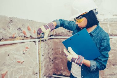 Woman working on new installations of bathroom pipes and using measuring tape - Image