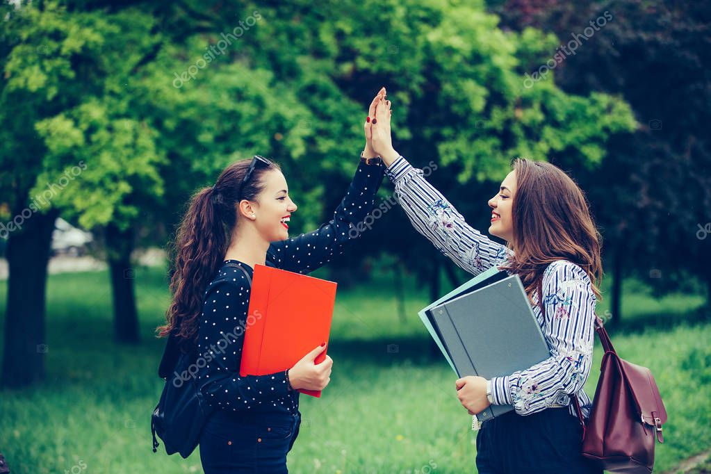 Two happy female students are giving high, celebrating success f