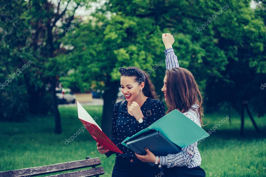 Two female friends, students celebrating success in a park