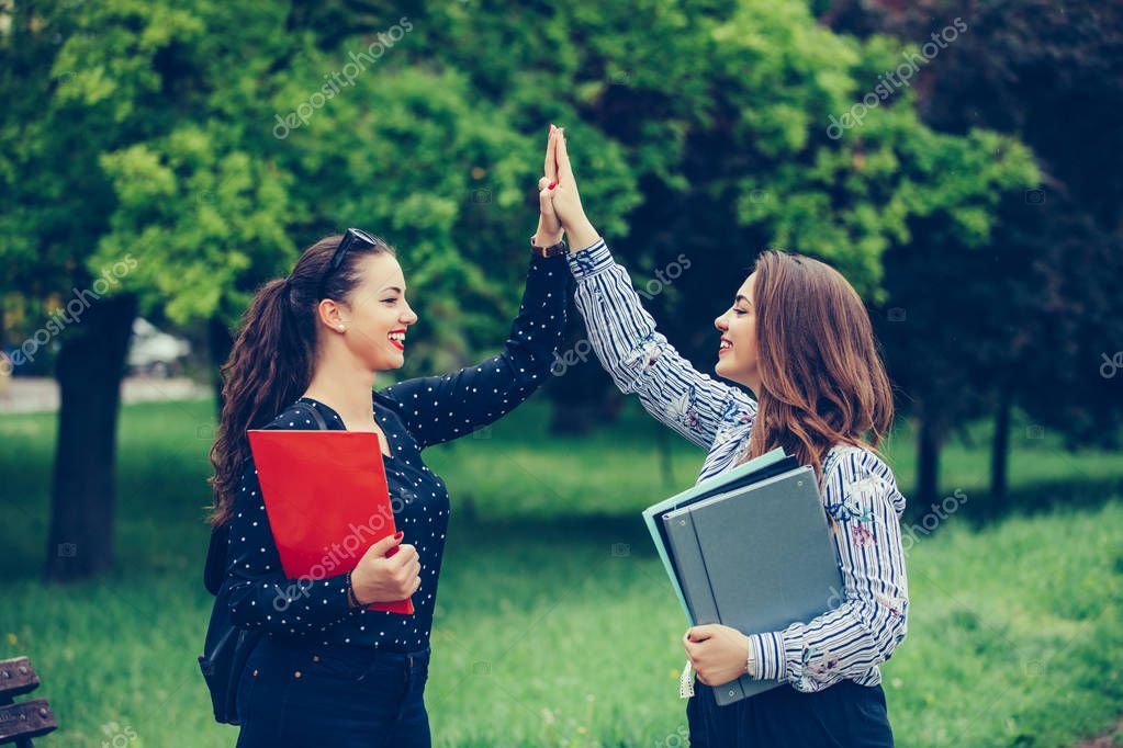 Two happy female students are giving high five after successfull