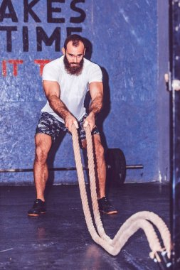 Bearded young man with battle ropes exercise in the fitness gym