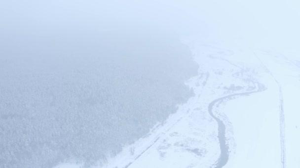 Flug auf eine Drohne über einen schmalen, gewundenen Fluss in der Nähe eines Waldes in einem verschneiten bewölkten Wintertag