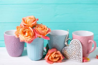 Bunch of fresh orange roses in cup and heart against turquoise wall