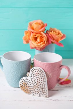 Two cups and orange roses against turquoise wall.