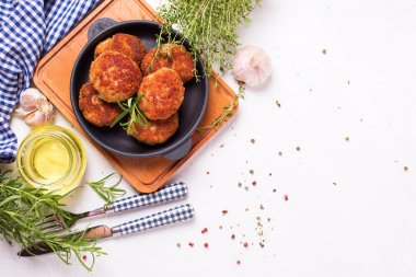 homemade cutlets and spices on frying pan on wooden background