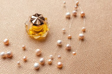 Pearl necklace and a perfume bottle on a gold background. Flat l