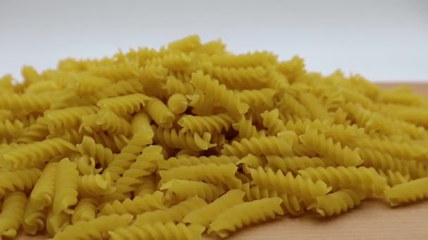 Raw Fusilli on wooden table. Traditional italian pasta.
