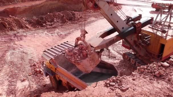 Kbelík velkého důlního vykopače zavádí obrovský náklaďák. Zobrazení zblízka, pohled shora.