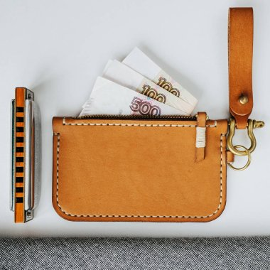 Wallet with money and a harmonica on a white background