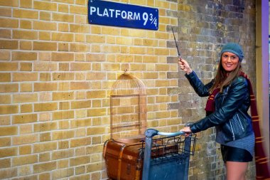 London, UK - May 12 2018: Unidentified people poses at the platform 9 3/4 that taken fron Harry Potter movie in King's Cross station