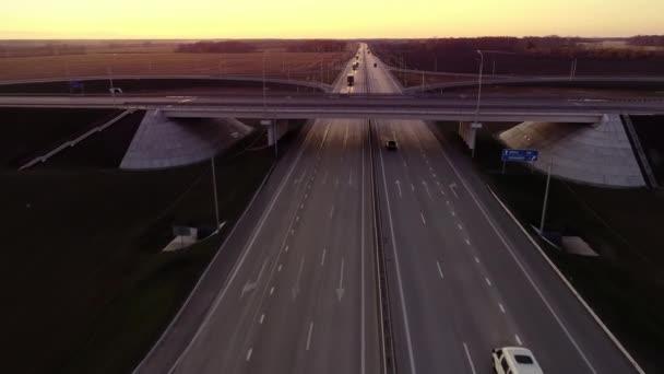 Náklaďáky jedoucí po dálnici. Highway top view při západu slunce večer. Auta jedou po asfaltové cestě. Letecký pohled