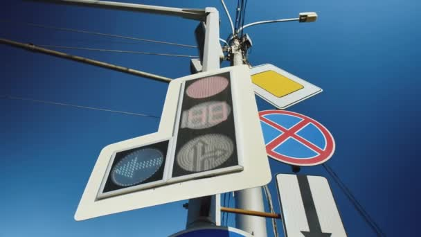 Close-up of a new traffic light and road signs against a blue sky background. Red traffic light.