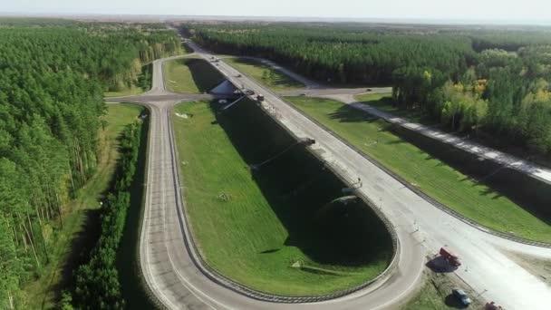 Flug eines Hubschraubers über eine Kreuzung mit fahrenden Autos und Lastwagen. Straßenkreuzung oder Autobahn im Nadelwald.