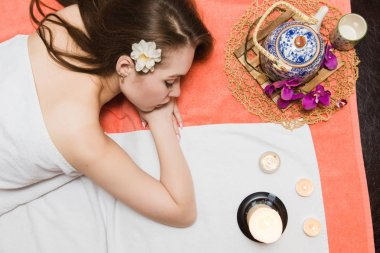 Young beautiful girl in spa salon. The girl lies on the couch for a massage after a rejuvenation procedure. a composition in Thai style with an orchid and a teapot with green tea. Flat lay