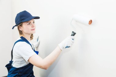 beautiful woman professionally paint the walls of the room. people in uniform, in overalls and a cap with a roller and brush, apartment renovation, interior design, tinting. isolated