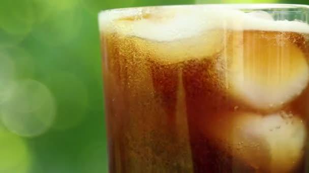 Nahaufnahme eines Glases mit einem erfrischenden Kaltgetränk mit Eisstücken und blubbernder Flüssigkeit auf einem verschwommenen sommerlichen Laubhintergrund
