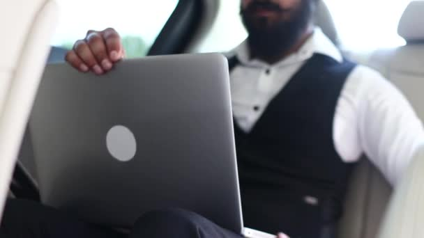 Indian businessman working with laptop in backseat of car