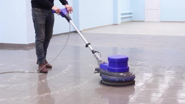 Der Reiniger wäscht einen Steg mit einer professionellen Poliermaschine. Fußbodenreinigung in der Lobby von Bürogebäuden
