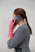 Egy kesztyűs lány mobilt tart a kezében..