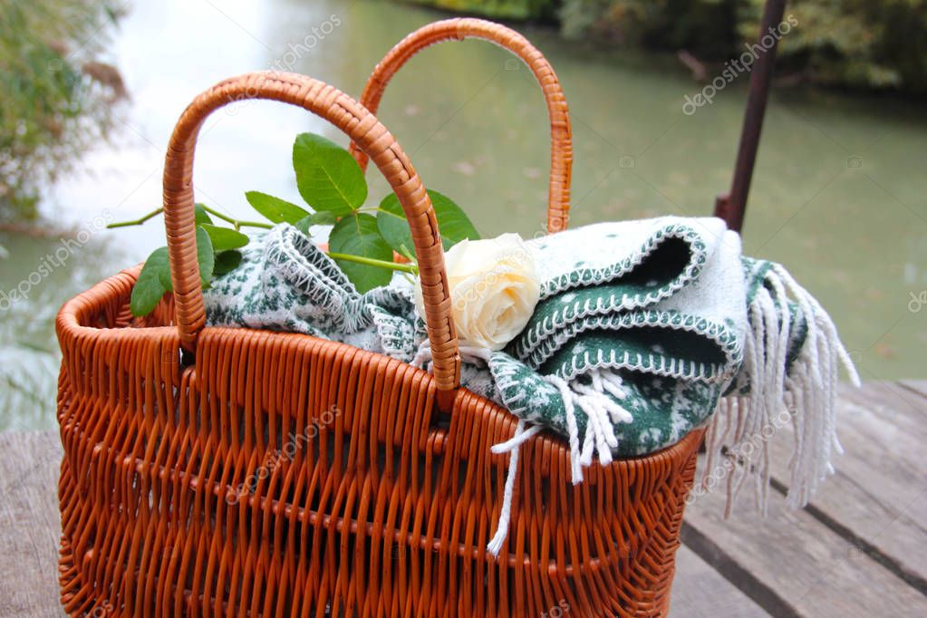Picnic basket on the background of the river. Plaid and rose in a wicker basket. A date in the park.