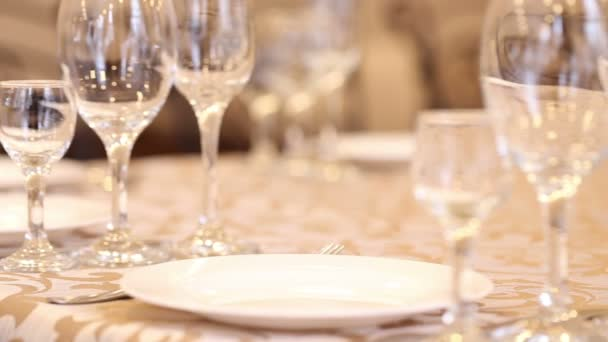Empty glasses set, fork, knife served for dinner in restaurant with cozy interior. Slow motion