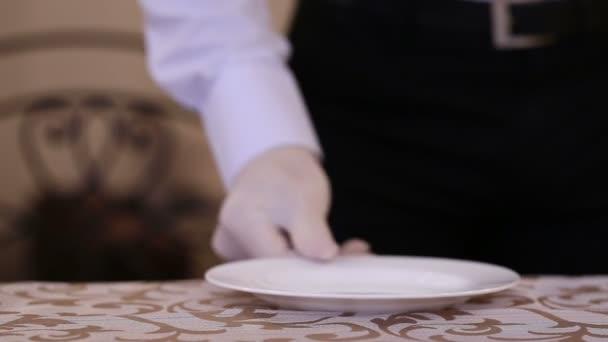 Mužské číšník uspořádá sada příborů na stole v restauraci. Restaurační stravovací služby
