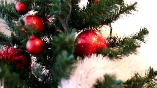 Vánoční strom zdobí červené ozdoby, bílé a červené věnec, Zlatá hvězda a jingle bells. Pohled z pohybu až dolů
