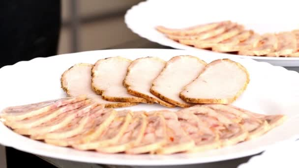 Cook arranges slices of baked meat and roulade of chicken on a white plate. Aperitif for the festive meal in restaurant