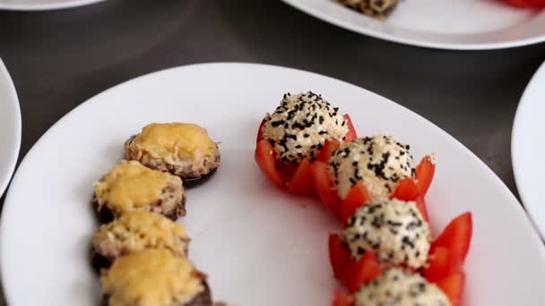Cheese balls with seeds and mushrooms stuffed with cheese laid out on a white plate. Preparation of snack for the festive meal in the restaurant
