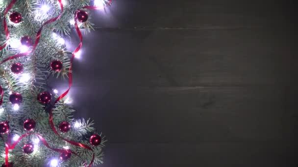 Vánoční pozadí černé dřevo zdobené s větvemi jedlí. Borovice se ozdoby červené konfety a mihotající světla. Pohled shora, prostor pro uvítací zprávu. Natočeno v rozlišení 4 k