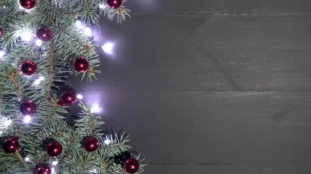 Vánoční pozadí černé dřevo zdobené s větvemi jedlí. Borovice jsou zdobeny cetky a brilantní světla. Pohled shora, prostor pro uvítací zprávu. Natočeno v rozlišení 4 k