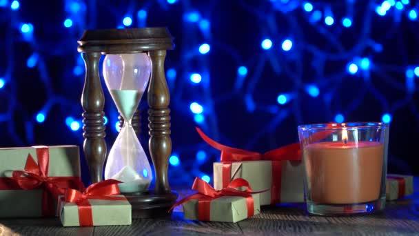 Karácsonyi háttér holiday elemek, égő gyertya, óra, ajándék, csillogó díszek. Idő,-a  a legjobb ajándék