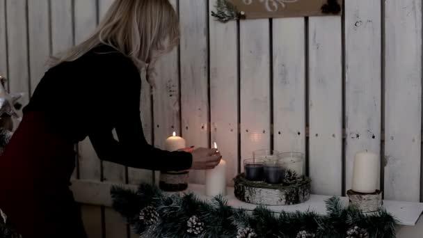 Eine Dame zündet Kerzen. Die Wärme und Atmosphäre im Winterurlaub. Xmas Dekoration. Weihnachten und glückliches neues Jahr
