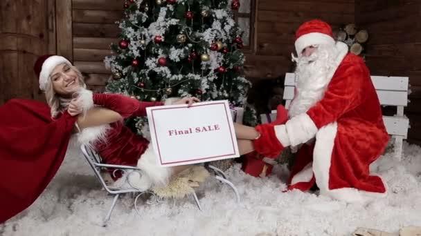 Santa Claus s jeho neteří, přineste poslední slevy pro zimní dovolenou. Poslední prodej. Vánoční atmosféru. Vánoce a šťastný nový rok